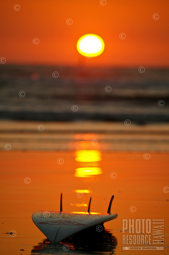 sun and surfboard reflection on the sandy beach under a beautiful orange and red sunset