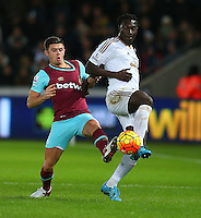 Aaron Cresswell of West Ham United and Bafetibis Gomis of Swansea City in action during the Barclays Premier League match between Swansea City and West Ham United played at The Liberty Stadium, Swansea on 20th December 2015