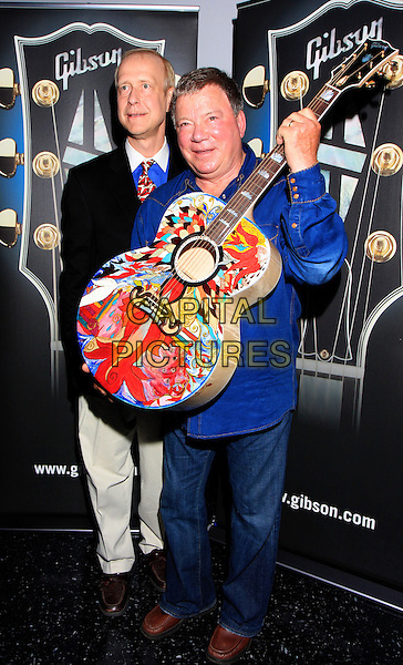 GIBSON CEO HENRY JUSZKIEWICZ, WILLIAM SHATNER  .at the special award/painted guitar presentation to William Shatner by Gibson Guitars at the Nashville Film Festival debut of Gonzo Ballet with a musical score composed by William Shatner (Star Trek, Boston Legal) and Ben Folds (Ben Folds Five)..Nashville, TN, USA, .April 17th 2009..full length guitar music blue shirt jeans .CAP/ADM/DH.©Dan Harr/AdMedia/Capital Pictures