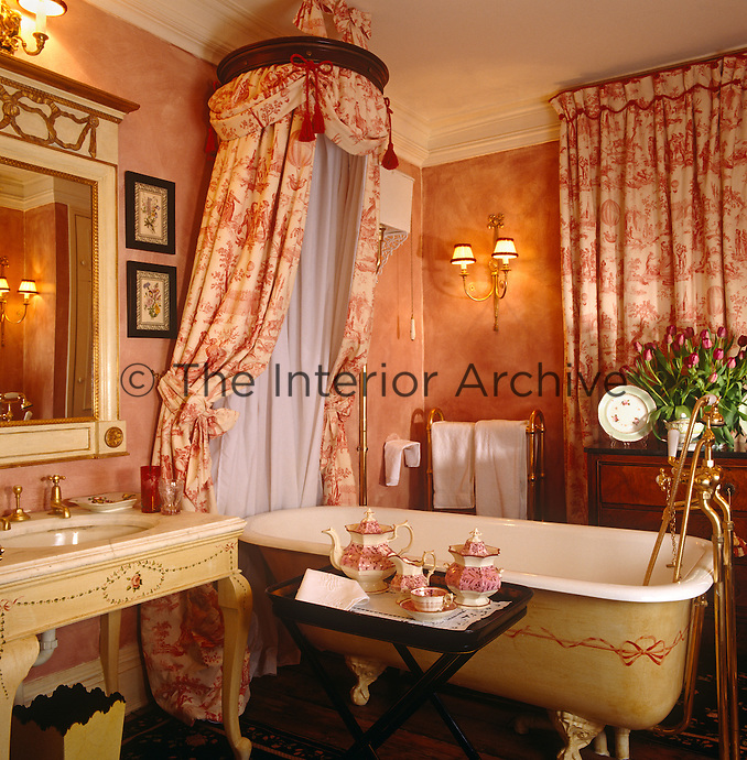 Tea is served on a tray in this sumptuous bathroom which features a toile de Jouy corona above the roll-top bath