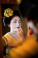 "Komomo, a maiko applying lipstick   <br /> Kyoto, Japan, 2005.<br /> Komomo is still an apprentice maiko, (""dance child"" or ""half-jewel"") and as part of her training spends twenty-four hours a day, seven days a week for about five years studying the formal arts such as dance, music, poetry. She follows her onee-san in the evenings but is paid considerably less than a geisha."