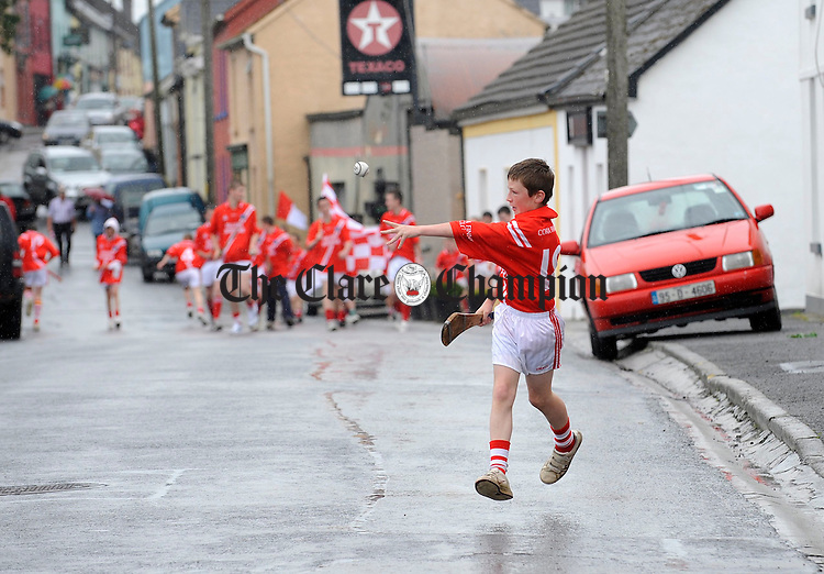 Corofin underage hurler Michael Shannon hurls his way down the street after taking part with his friends in the Munster GAA council Torch Run from Carron th Thurles. Photograph by John Kelly.