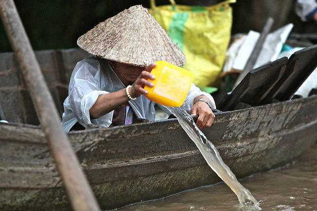 A woman bails water from her boat at the Cai Rang floating market, in the Mekong Delta, south of Can Tho, Vietnam. Sept. 30, 2011.