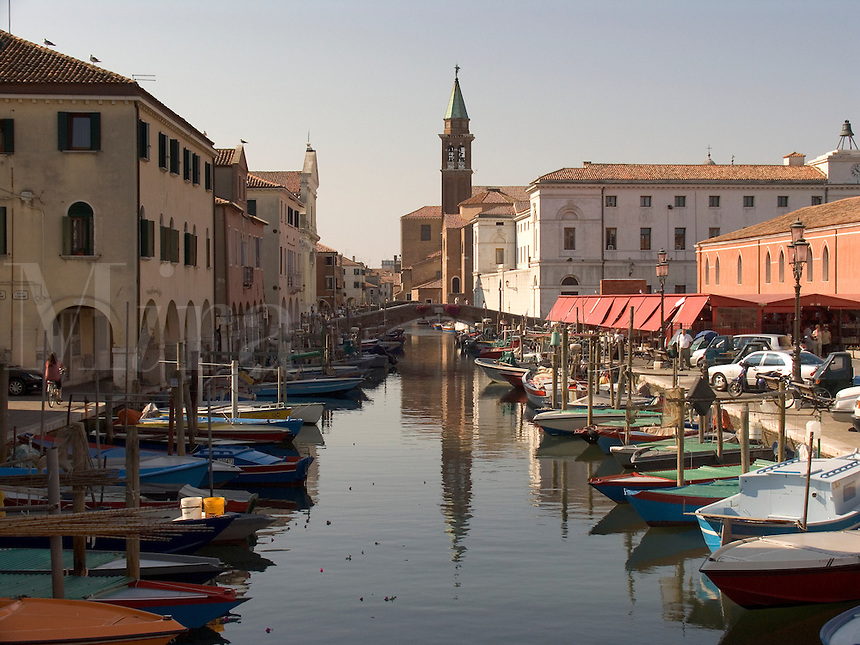 Fishing boats and houses along Vena canal in Chioggia Ital