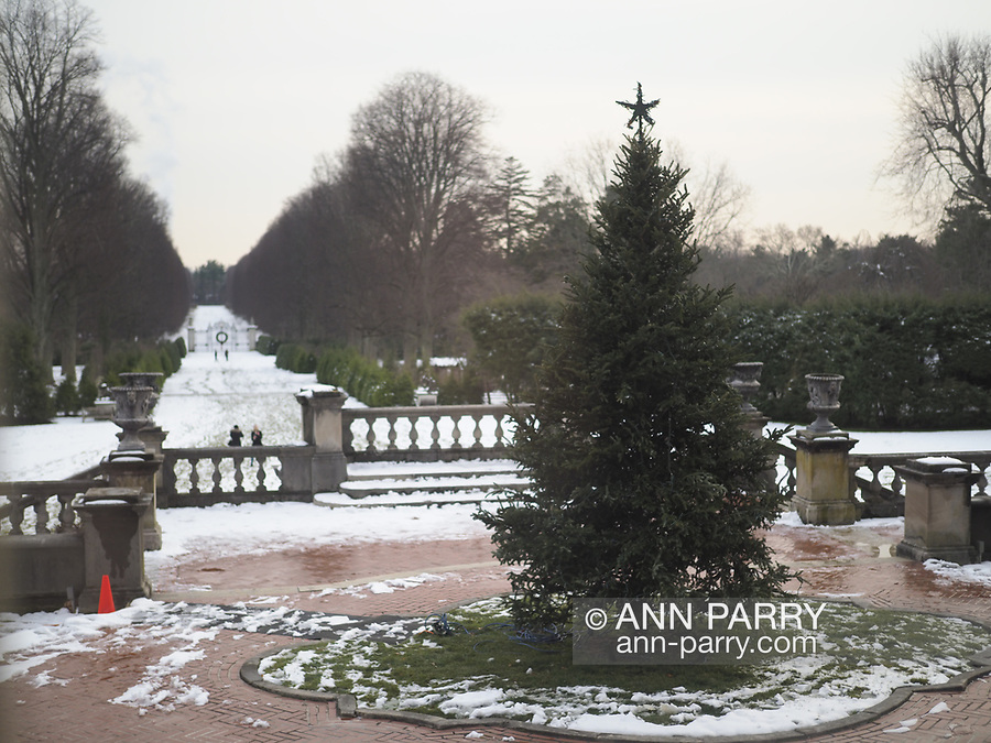 Old Westbury, New York, USA. December 17, 2017. Old Westbury Gardens musem, a former estate of John Shaffer Phipps, welcomes visitors during snowy winter holiday weekend. Westbury House rooms had lit fireplaces, and were decorated with Christmas Trees, a train set in bedroom, deer family watching doe take bubble bath in bathroom, and more festive decorations. Cider and cookies were served in large sunroom.