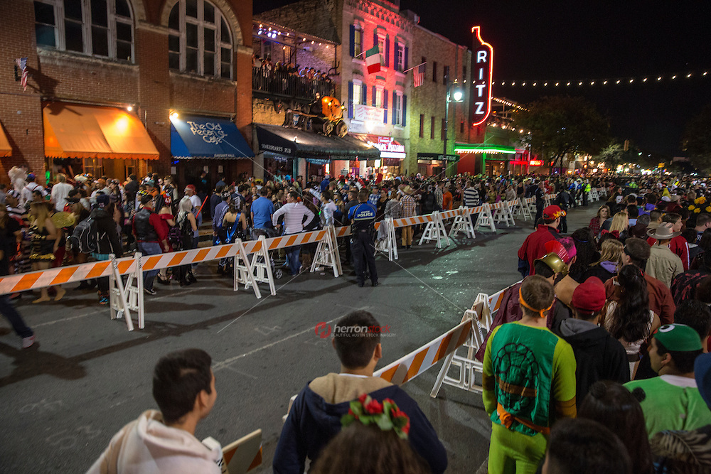 Austin Police Department (ADP) maintain order with barricade perimeter control checkpoints as thousands gather for Halloween festivities on 6th Street in downtown Austin, Texas.