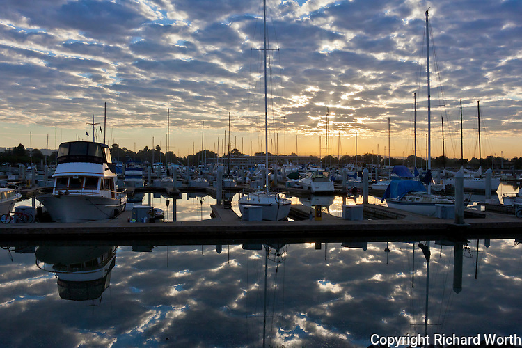 Looking like tortoise shells, mottled morning clouds reflect in the water at San Leandro Marina, silent  moored boats their sole witness.