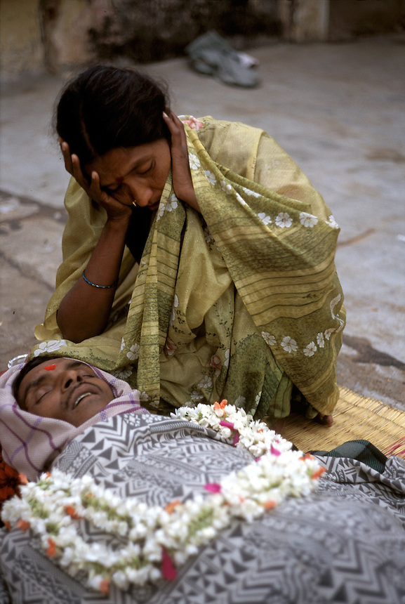 A widow mourns over the body of her dead husband in Mysore, India, shortly after his death from undetermined causes. As the family's only bread-winner, his death had grave consequences for the family economy.