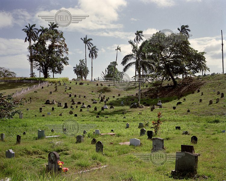 Headstones scattered on a hillside at the Mount Hope Cemetery (Cementerio de Monte Esperanza) in Colon, where 'Silver Roll' (Afro-Antillean, non-US, non-white) workers and their dependents were buried during and after the construction period of the Panama Canal (1904-1914).  <br /> <br /> The Panama Canal Zone is an area extending 8kms out, in each direction, from the waterway's central line, was a territory controlled by the United States between 1903 and 1979. After a 20 year period of joint administration, the Canal came under the full control of Panama in 1999. The Canal opened to shipping in 1914 and during its tenure was of great strategic importance to the US, enabling it to rapidly move its naval fleet between the Atlantic and Pacific Oceans. However, its economic value came not directly from shipping fees but from the stimulus to trade that the waterway created. One hundred years after it opened in 2014 it is due to have its locks upgraded to cater for the super sized container ships of the 21st Century.  <br /> During the era of American administration thousands of US citizens populated the Canal Zone, living and working under US law in towns built to American standards. Not all of these people returned north after the canal came under full Panamanian control many stayed on, their identities tied to the region.