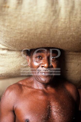 Ilheus, Brazil. Cacau porter (man carrying sack of cacau beans used in chocolate manufacture.)