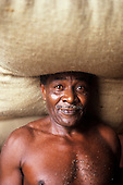 Ilheus, Brazil. Cacau porter (man carrying sack of cacau beans used in chocolate manufacture.)