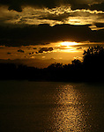 The golden summer sun sets across McKay Reservoir in Broomfield, Colorado.