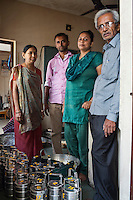 Archana (2nd from right) and her husband (2nd from left) poses for a family portrait with her husband's parents in her house in Anand, Gujarat, India on 11th December 2012. Archana , an ex-surrogate, continues to work with Dr. Nayana Patel, catering specially prepared tiffin meals to the surrogates and Akanksha IVF and Surrogacy clinic staff which she prepares with her family. Photo by Suzanne Lee / Marie-Claire France