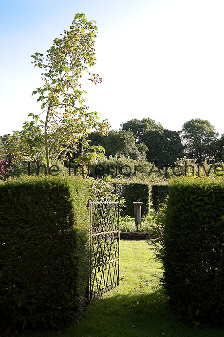 A wrought iron gate opens into an area of the garden enclosed by clipped hedges with a sundial at its centre