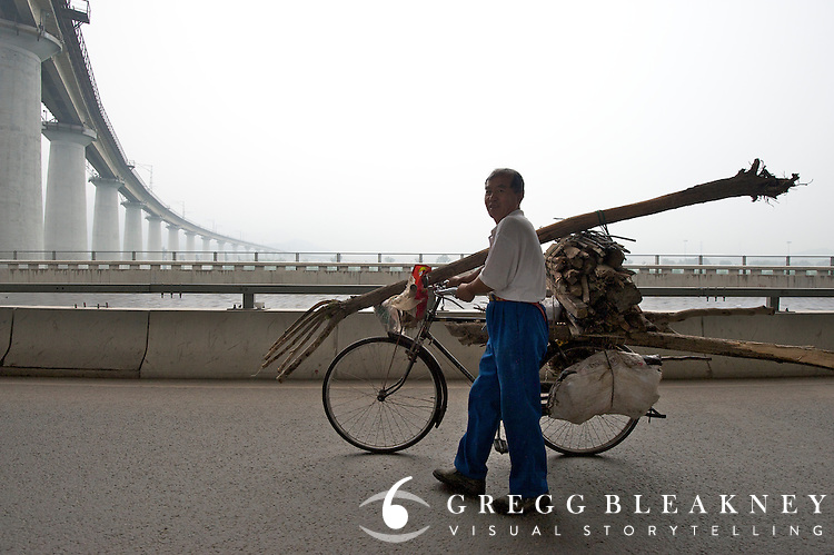 A man uses a bicycle to haul wood along  stage 2 -- 133.5km from the Bird's Nest in Beijing to Mentougou via North Gate of Summer Palace. 2011 Tour of Beijing Scouting Photos