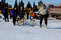 Volunteer checker Steve Kovach of McGrath helps lead Allen Moore out of the Elim checkpoint during the 2010 Iditarod
