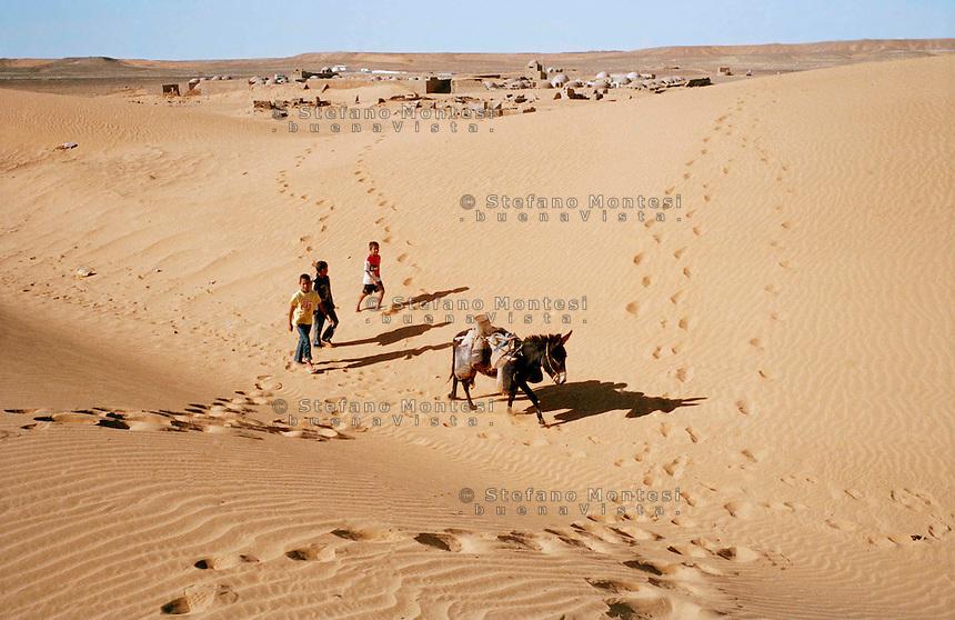 Febbraio 2012. Ragazzi saharawi portano l'acqua con l'asino attraverso il deserto del Sahara vicino al campo profughi saharawi di  Dakhla, Algeria<br /> February 2012. Sahrawi children carry water with a donkey through the Sahara Desert near the Sahrawi refugee camp in Dakhla, Algeria.