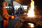 Foto: VidiPhoto<br /> <br /> ANDELST – Kinderen uit het hele land togen zaterdag naar smederij Mondra in het Betuwse Andelst, om daar in de praktijk kennis te maken met het smidsvak. Met behulp van bevriende smeden, zorgde eigenaar Cees Pronk er voor dat de jeugd -voorzien van beschermende kleding- zelf hamer en aanbeeld mochten hanteren om metalen sleutelhangers te vervaardigen. De nationale open bedrijvendag met de naam Backstage was georganiseerd door een educatief tv-programma. Kinderen konden in het hele land bij tal van bedrijven een kijkje achter de schermen nemen. Mondra was de enige smederij die zijn deuren open zette. Opmerkelijk is de sterk toegenomen belangstelling van meisjes voor het vak van smid.