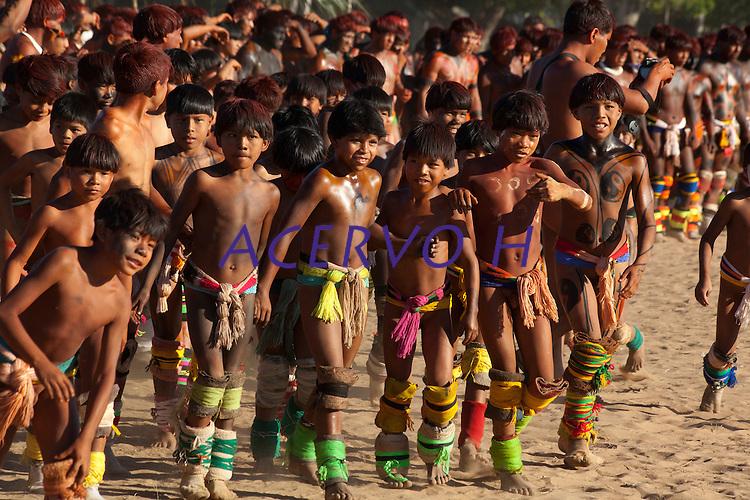 Lutadores de diversas aldeias se preparam para o Huka-huka.<br /> <br /> Huka-hukaLuta corporal que na terminologia kamaiurá lembra os gritos dos lutadores ao se defrontarem imitando o rugido da onça. Os anfitriões enfrentam uma aldeia convidada de cada vez, começando por lutas individuais de campeões reconhecidos. Seguem-se lutas simultâneas de vários pares de rivais, até as lutas dos muito jovens. Os lutadores se defrontam batendo o pé direito no chão, dando voltas no sentido dos ponteiros do relógio, com o braço esquerdo estendido e o direito retraído, enquanto gritam alternadamente: hu! ha! hu! ha! Até que chocam as mãos direitas e enlaçam o pescoço do adversário com a esquerda. A luta, que pode durar poucos segundos, termina quando um dos adversários é derrubado, o que não tem que ocorrer literalmente, bastando que a parte posterior de um de seus joelhos seja agarrada pela mão do outro, o que é considerado condição suficiente para provocar-lhe a queda. As aldeias convidadas não lutam entre si. Os enfeites dos troncos do Kwarup podem ser dados aos lutadores vencedores e também aos dois tocadores de maracá..<br /> Querência, Mato Grosso, Brasil. <br /> 26/07/2015<br /> <br /> Fonte: ISA