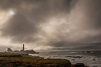 Mist and fog surround the Pigeon Point LIght House while the cloud-filtered sun looks down along the California coast south of San Francisco.