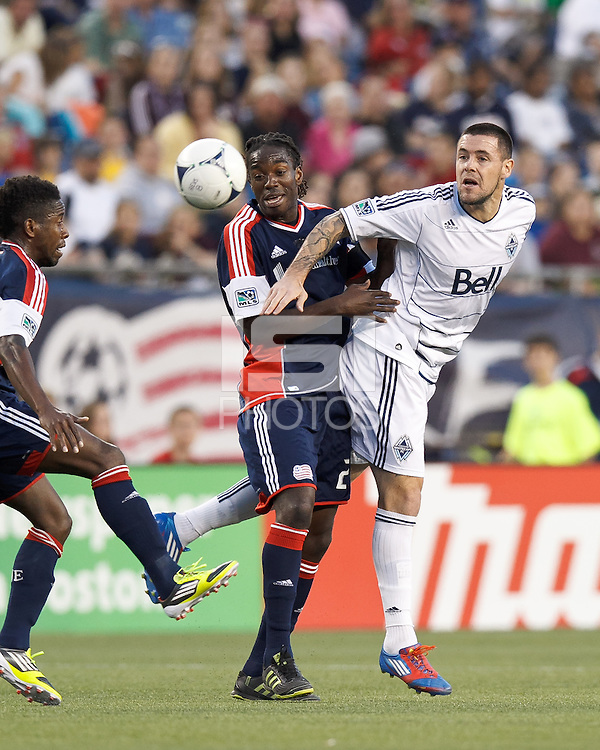 Vancouver Whitecaps FC forward Eric Hassli (29) heads the ball as New England Revolution midfielder Shalrie Joseph (21) pressures. In a Major League Soccer (MLS) match, the New England Revolution defeated Vancouver Whitecaps FC, 4-1, at Gillette Stadium on May 12, 2012.