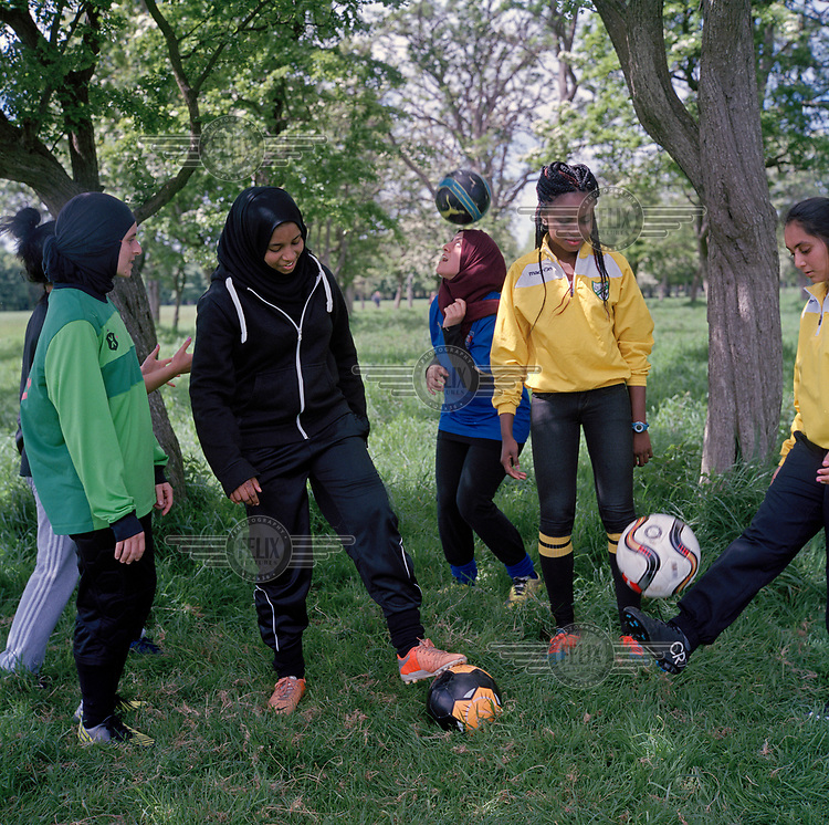 Young Muslim girls and friends playing football in Phoenix Park.