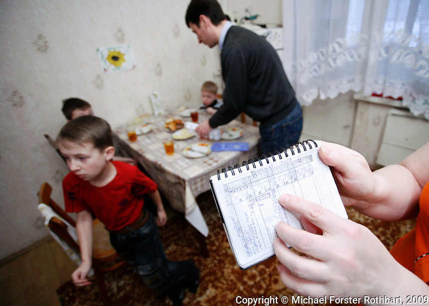 &ldquo;The Bible gives us fortitude.&rdquo; &mdash; Eduard Evteev, manager at the Chernobyl Training Center<br /> <br /> Morning rush in the Evteevs&rsquo; kitchen: Tanya checks her work schedule while her family finishes breakfast. Her husband, Eduard, was diagnosed with a kidney tumor but recovered after surgery. He is a man of faith. &ldquo;My belief was a support,&rdquo; he says. &ldquo;God gives us life and has the right to take it away.&rdquo; Now Tanya is a janitor at the plant, working three or four 12-hour shifts a week.<br /> ------------------- <br /> This photograph is part the book of Would You Stay?, by Michael Forster Rothbart, published by TED Books in 2013. The photos come from Forster Rothbart&rsquo;s two long-term documentary photography projects, After Chernobyl and After Fukushima.<br /> &copy; Michael Forster Rothbart 2007-2013.<br /> www.afterchernobyl.com<br /> www.mfrphoto.com &bull; 607-267-4893 &bull; 607-436-2856<br /> 34 Spruce St, Oneonta, NY 13820<br /> 86 Three Mile Pond Rd, Vassalboro, ME 04989<br /> info@mfrphoto.com<br /> Photo by: Michael Forster Rothbart<br /> Date:  2/2009    File#:  Canon 5D digital camera frame 55663<br /> -------------------