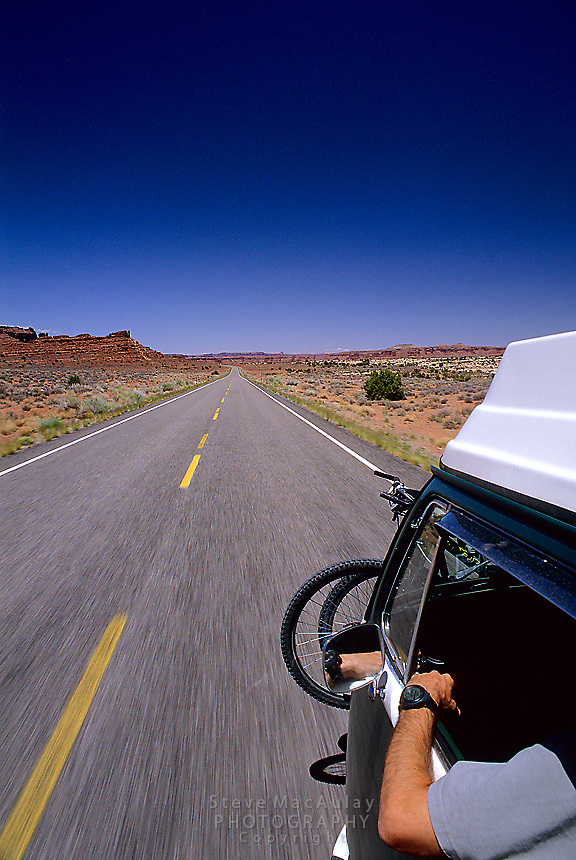 POV shot of Volkswagen camper bus speeding down a deserted desert highway, South East Utah.