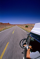 POV shot of Volkswagen camper bus speeding down a deserted desert highway, South East Utah.
