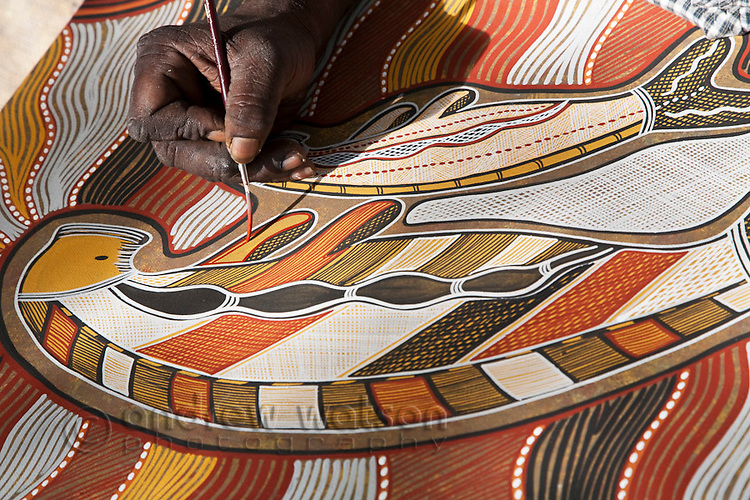 Man painting indigenous artwork of a dugong.  Cooktown, Queensland, Australia