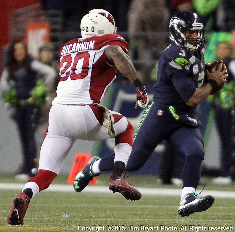 Seattle Seahawks quarterback Russell Wilson scrambles against Arizona Cardinals safety Deone Johnson (20) at CenturyLink Field in Seattle, Washington on November 15, 2015. The Cardinals beat the Seahawks 39-32.   ©2015. Jim Bryant photo. All Rights Reserved.