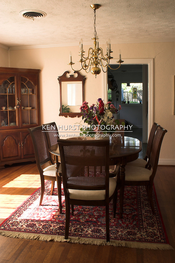 dining room table and chairs with bright sunlight streaming in through large window