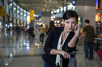 Young pretty stylish woman in the terminal takes a call on her cell phone at the Austin International Airport.