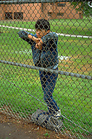 Cambodian/Am age 15 at school with travel bag looking thru fence.  St Paul Minnesota USA