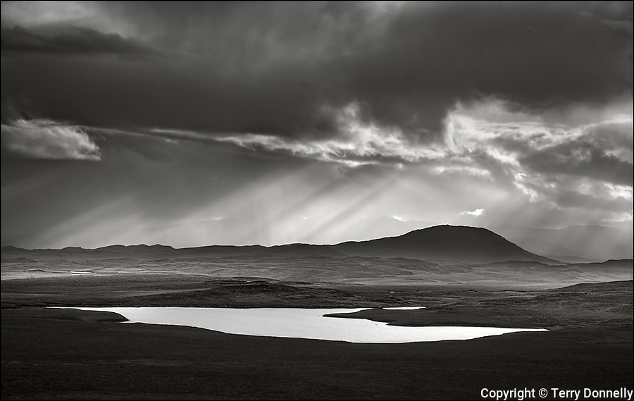Scotland, Isle of Lewis and Harris: Approaching storm clouds with sun rays and reflections on a small lake