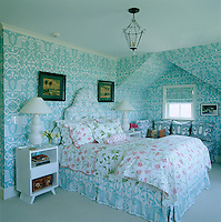 In the master bedroom the headboard and wall coverings are by China Seas complemented with feminine floral bed linen