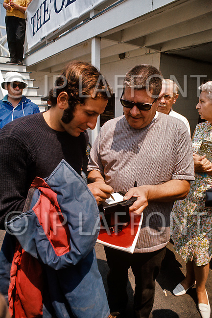 Newport RI, US - July 7, 1972. French navigator Alain Colas signs autographs after winning the 1972 Transat Plymouth-Newport race. Alain Colas (September 16, 1943 - November 16, 1978) was the first sailor to complete a solitary round the world race in a multihull and endeavored to complete the 1978 Route du Rhum, however disappeared in the Atlantic after passing Azores.