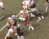 Washington Redskins quarterback Jay Schroeder (10) looks for a receiver during the game against the Los Angeles Raiders at RFK Stadium in Washington, D.C. on September 14, 1986.  The Redskins won the game 10 - 6.  <br /> Credit: Arnold Sachs / CNP