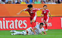 Abby Wambach (C) of Team USA and Ri Ye Gyong of North Korea during the FIFA Women's World Cup at the FIFA Stadium in Dresden, Germany on June 28th, 2011.