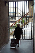 An elderly woman with a shopping trolley in an alley leading to Church Street Library in Paddington, London.