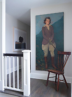 On the hallway landing an antique wooden chair stands in front of a striking portrait painting.
