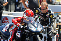 Jul. 17, 2010; Sonoma, CA, USA; NHRA pro stock motorcycle rider Matt Smith (right) gives makes an adjustment to the bike of wife Angie Smith during qualifying for the Fram Autolite Nationals at Infineon Raceway. Mandatory Credit: Mark J. Rebilas-
