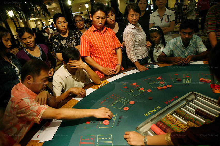 Phnom Penh's Nagaworld Casino and five-star hotel is one of Cambodia's biggest private employers with more than 3,000 staff catering for a stream of visitors. It functions non-stop 24 hours a day with an inside airconditioned controlled temperature of 21 degrees.It is a 14 storey hotel and entertainment complex, with more than 500 bedrooms, 14 restaurants and bars, 700 slot machines and 200 gambling tables. There is also a spa, karaoke and VIP suites, live bands, and a nightclub. Its monolithic building dominates the skyline at the meeting point of the Mekong and Tonle Sap rivers, in stark contrast to nearby intricate Khmer architecture.///Chinese and Asian guests gambling at casino tables of Nagaworld