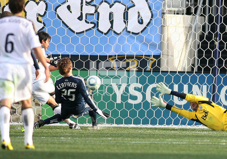Carlos Ruiz#20 of the Philadelphia Union beats Jonathan Leathers#25 and Joe Cannon#1 of the Vancouver Whitecaps to score during an MLS match at PPL Park in Chester, PA. on March 26 2011. Union won 1-0.
