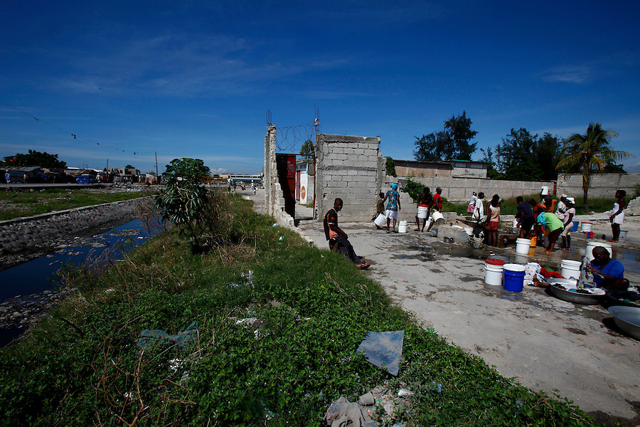 Nov 10, 2010 - Port-au-Prince, Haiti.Residents of the Cite Soleil area of Port-au-Prince, Haiti gather water from a well just yards away from a river of human waste and garbage  on Wednesday, November 10, 2010 as fears of a Cholera outbreak spread through the area just two days after cases of the infection were confirmed in the area, the poorest slum in Haiti's capital. Officials from the Pan American Health Organization warn that Haiti's cholera epidemic, spread primarily through consuming infected water and food, is likely to grow much larger in the wake of Hurricane Tomas.  (Credit Image: Brian Blanco/ZUMA Press)