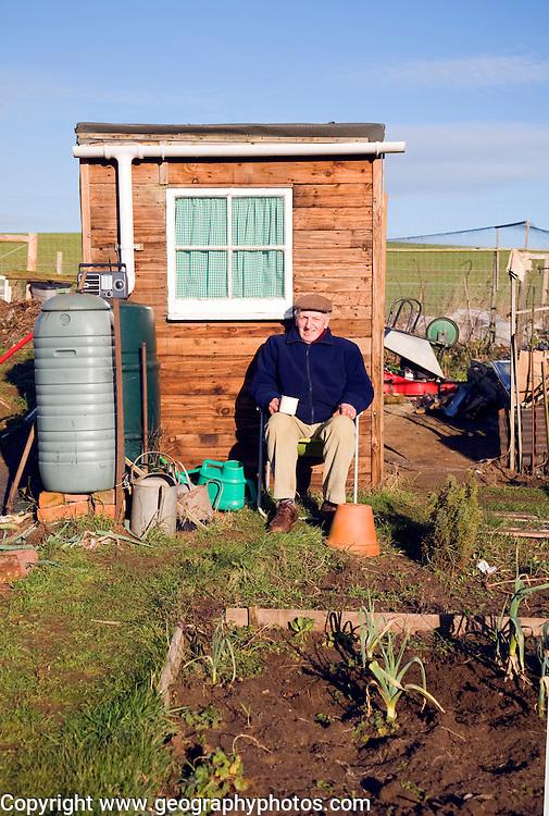 Man sitting in front of his allotment garden shed, Shottisham, Suffolk, England