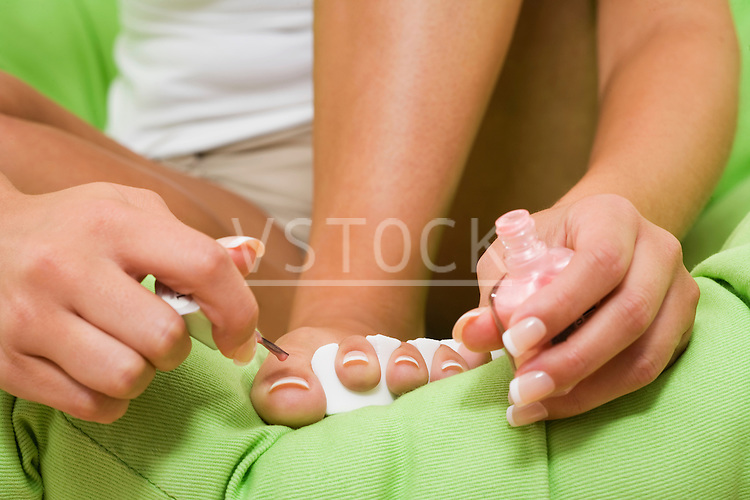 Woman applying nail polish to toes, close up, low section