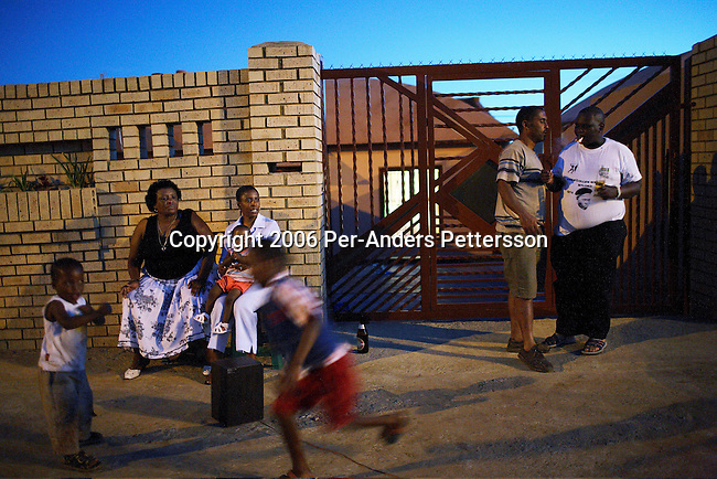 SOWETO, SOUTH AFRICA OCTOBER 22: Tina Pasomane (l), age 55, sits outside a house with relatives and friends on October 22, 2006 in the Orlando West section of Soweto, Johannesburg, South Africa. Tina owns a shebeen (bar), a few houses away, and she is a popular person in this neighborhood. Soweto is South Africa?s largest township and it was founded about one hundred years to make housing available for black people south west of downtown Johannesburg. The estimated population is between 2-3 million. Many key events during the Apartheid struggle unfolded here, and the most known is the student uprisings in June 1976, where thousands of students took to the streets to protest after being forced to study the Afrikaans language at school. Soweto today is a mix of old housing and newly constructed townhouses. A new hungry black middle-class is growing steadily. Many residents work in Johannesburg but the last years many shopping malls have been built, and people are starting to spend their money in Soweto.  .(Photo by Per-Anders Pettersson/Getty Images).