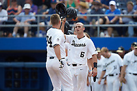 Gavin Sheets (24) of the Wake Forest Demon Deacons is greeted at home plate by teammate Jake Mueller (6) after hitting a home run against the Florida Gators in Game Two of the Gainesville Super Regional of the 2017 College World Series at Alfred McKethan Stadium at Perry Field on June 11, 2017 in Gainesville, Florida.  (Brian Westerholt/Four Seam Images)