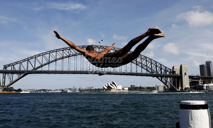 A man dives into Sydney Harbour from a ferry wharf on a hot day